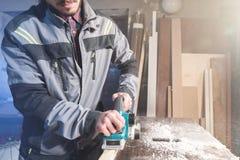 Jonge timmerman met een baard die met een elektrisch vliegtuig met zuiging die van zaagsel werken en houten bars nivelleren schur royalty-vrije stock fotografie