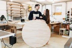 Jonge timmerman in timmermansworkshop De man houdt een houten ronde raad voor de tekst Copyspace jonge specialist, opstarten stock afbeeldingen