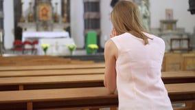 Jonge toegewijde godsdienstige vrouw die in katholieke kerk bidden Gelovige katholiek bij Europese kathedraal stock videobeelden