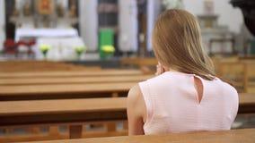 Jonge toegewijde godsdienstige vrouw die in katholieke kerk bidden Gelovige katholiek bij Europese kathedraal stock video