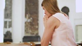 Jonge toegewijde godsdienstige vrouw die in katholieke kerk bidden Gelovige katholiek bij Europese kathedraal stock footage