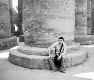 Jonge toerist die bij de basis van een oude Egyptische pijler wordt gezeten stock afbeeldingen