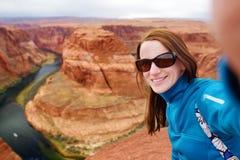 Jonge toerist die een foto van zich nemen door beroemde Hoefijzerkromming, Arizona stock foto