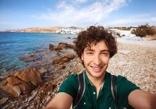 Jonge toerist die selfie op Mykonos-strand, Griekenland nemen stock afbeelding