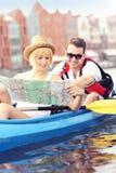 Jonge toeristen met een kaart in een kano royalty-vrije stock afbeelding