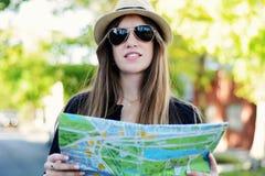 Jonge toeristenvrouw die een kaart bekijken stock fotografie
