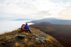Jonge toeristenwandelaar met rugzak die en op de bovenkant van de berg situeren ontspannen en de mooie gele herfst bekijken Royalty-vrije Stock Foto