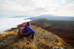 Jonge toeristenwandelaar met rugzak die en op de bovenkant van de berg situeren ontspannen en de mooie gele herfst bekijken Stock Foto's