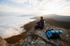 Jonge toeristenwandelaar met rugzak die en op de bovenkant van de berg situeren ontspannen en de mooie gele herfst bekijken Stock Afbeeldingen