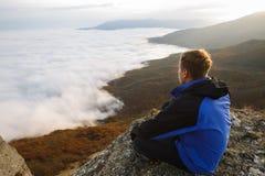 Jonge toeristenwandelaar met rugzak die en op de bovenkant van de berg situeren ontspannen en de mooie gele herfst bekijken Royalty-vrije Stock Afbeelding