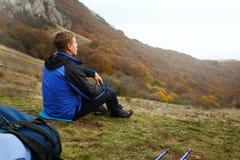 Jonge toeristenwandelaar met rugzak die en op de bovenkant van de heuvel in bergen situeren ontspannen en mooi bekijken Stock Foto
