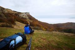 Jonge toeristenwandelaar met rugzak die en op de bovenkant van de heuvel in bergen situeren ontspannen en mooi bekijken Royalty-vrije Stock Fotografie