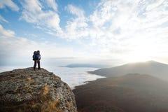 Jonge toeristenwandelaar met rugzak die zich op de bovenkant van de berg bevinden en mooi geel de herfstlandschap bekijken Stock Afbeelding