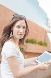 Jonge toevallige bedrijfsvrouw die tablet op een onderbreking gebruiken Stock Foto