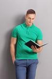 Jonge toevallige mens die een boek lezen royalty-vrije stock foto