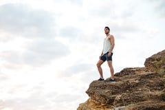 Jonge toevallige mens die zich op de bergrots bevinden Stock Foto