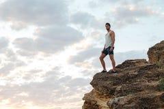 Jonge toevallige mens die zich op de bergrots bevinden Stock Foto's