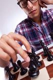 Jonge toevallige mens die zijn schaakstuk beweegt Stock Foto's