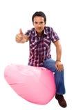 Jonge toevallige mens gezet in een kleine roze bank Royalty-vrije Stock Foto