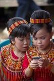 Jonge Torajan-meisjes die een braambessen mobiele telefoon bekijken Stock Foto