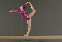 Jonge turner op evenwichtsbalk Stock Afbeelding
