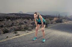Jonge uitgeputte sportvrouw die in openlucht bij asfaltweg de ademhaling lopen stock foto