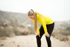 Jonge uitgeputte sportvrouw die in openlucht bij de vuile weg ademhaling lopen stock foto's