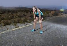 Jonge uitgeputte sportvrouw die in openlucht op het einde van de asfaltweg voor ademhaling lopen en een rust na massieve inspanni royalty-vrije stock foto's