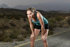 Jonge uitgeputte sportvrouw die in openlucht op het einde van de asfaltweg voor vermoeide ademhaling lopen stock foto's