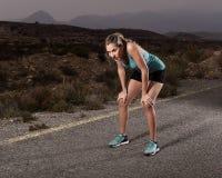 Jonge uitgeputte sportvrouw die in openlucht op het einde van de asfaltweg voor vermoeide ademhaling lopen royalty-vrije stock foto