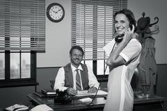 Jonge uitstekende de telefoonontvanger van de secretaresseholding Stock Foto