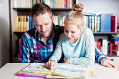 Jonge vader die haar dochter met schoolproject thuis helpen stock foto's