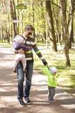 Jonge vader die met tweelingkinderwagen in het park lopen stock foto