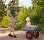 Jonge vader die met zijn kleine zoon lopen Stock Afbeelding
