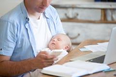 Jonge vader die pasgeboren kind houden en mobiele telefoon met behulp van stock afbeeldingen