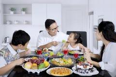 Jonge vader die zijn dochter in de keuken voeden Royalty-vrije Stock Afbeeldingen