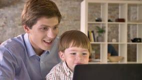 Jonge vader die zijn glimlachende zoon houden en laptop bekijken, die in modern gelukkig bureau zitten, stock video