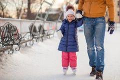 Jonge vader die zijn kleine dochter onderwijzen om te schaatsen stock afbeelding