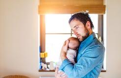 Jonge vader die zijn pasgeboren babyzoon in zijn wapen houden Royalty-vrije Stock Foto