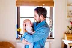 Jonge vader die zijn pasgeboren babyzoon in zijn wapen houden Stock Foto