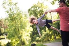 Jonge vader die zijn zoon spinnen Zonnige de zomeraard stock foto
