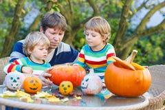 Jonge vader en twee kleine zonen die hefboom-o-lantaarn voor hallo maken Royalty-vrije Stock Afbeelding