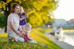 Jonge vader en zijn dochters die door een rivier zitten stock foto's