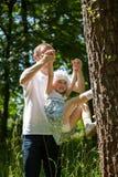 Jonge vader en zijn gelukkige kleine dochter die in een park spelen Royalty-vrije Stock Fotografie