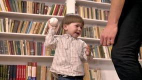 Jonge vader en zijn kleine zoon die met bal, gelukkig glimlachen spelen, planken met boekenachtergrond stock footage