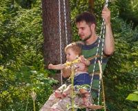Jonge vader en zijn kleine zoon op de schommeling Stock Afbeelding