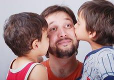 Jonge vader en zijn twee jongens die hem kussen Stock Foto