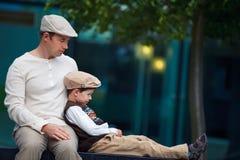 Jonge vader en zoon die rust in openlucht in stad hebben Stock Foto's