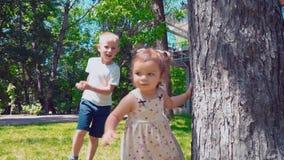 Jonge vader met kinderen die rond een boom dichtbij de huis, Papa, zoons en babydochter lopen die pret in de binnenplaats hebben stock video