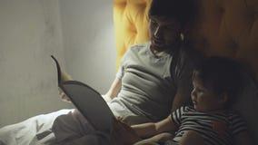 Jonge vader met weinig zoon die op bed liggen thuis en fairytale boek lezen vóór het slapen in avond stock videobeelden